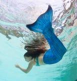 Modelez dans une piscine portant un mermaid& x27 ; queue de s Photos stock