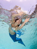 Modelez dans une piscine portant un mermaid& x27 ; queue de s Image stock