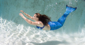 Modelez dans une piscine portant un mermaid& x27 ; queue de s Photo stock