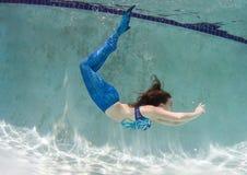Modelez dans une piscine portant un mermaid& x27 ; queue de s Images libres de droits