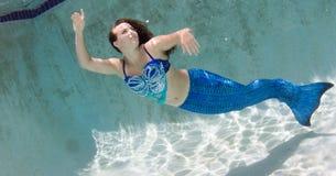 Modelez dans une piscine portant un mermaid& x27 ; queue de s Images stock