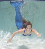 Modelez dans une piscine utilisant une queue du ` s de sirène Photos libres de droits