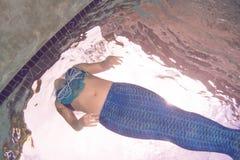 Modelez dans une piscine utilisant une queue du ` s de sirène Image libre de droits