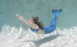 Modelez dans une piscine utilisant une queue du ` s de sirène Photo stock