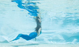 Modelez dans une piscine utilisant une queue du ` s de sirène Image stock