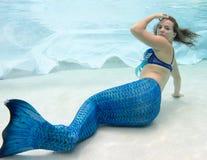 Modelez dans une piscine utilisant une queue du ` s de sirène Photo libre de droits