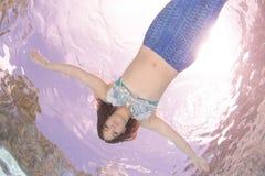 Modelez dans une piscine utilisant une queue du ` s de sirène Images libres de droits