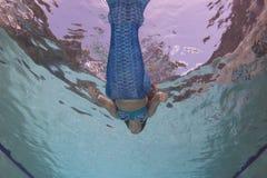 Modelez dans une piscine utilisant une queue du ` s de sirène Images stock