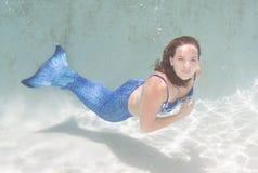 Modelez dans une piscine utilisant une queue du ` s de sirène Photographie stock libre de droits