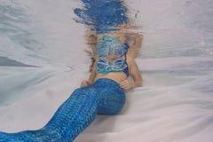 Modelez dans une piscine utilisant une queue du ` s de sirène Photos stock