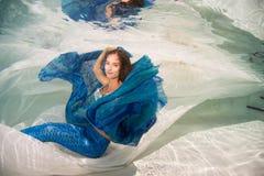 Modelez dans une piscine utilisant une queue du ` s de sirène Photographie stock