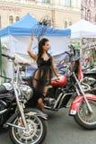 Modelez dans une robe transparente posant dans une moto rouge Photos stock