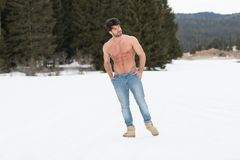Modelflexing muscles outdoors in Aard stock foto's