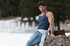 Modelflexing muscles outdoors in Aard royalty-vrije stock foto