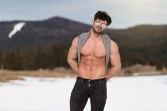 Modelflexing muscles outdoors in Aard stock fotografie
