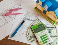 Modelhouse, räknemaskin och US dollar på konstruktionsplanläggning Arkivfoton