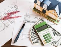 Modelhouse, räknemaskin och US dollar på konstruktionsplanläggning Royaltyfri Fotografi