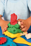 Modeling clay. Child playing with modeling clay on a blue table Royalty Free Stock Photo
