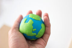 Modeling clay globe in hand. Royalty Free Stock Photo
