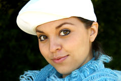 Modeling a look. Attractive Mexican model wearing blue scarf and white cap with expressive eyes and mouth with black background Stock Photos