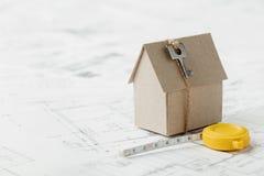 Modelkartonhuis met sleutel en meetlint op blauwdruk De huisbouw, architecturale en bouwontwerpconcept Stock Foto