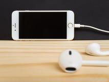 Modell Apples iPhone7 und Modell Apples EarPods Stockfotografie