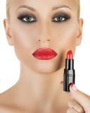 Modell auf dem weißen Hintergrund, der roten Lippenstift anwendet Lizenzfreies Stockbild
