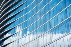 Modell av blåa exponeringsglas i hög byggnad med skugga av molnet A Arkivfoto