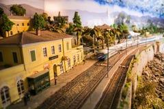 Modell av den lilla järnvägsstationen med att att närma sig för drev fotografering för bildbyråer
