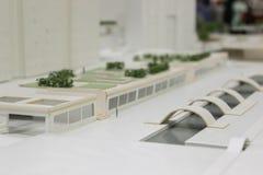 Modell av en byggnad och en parkera Arkivfoto
