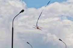Modell av ett biplanflygplan i den stads- himlen mot bakgrunden av moln och lyktor royaltyfria bilder