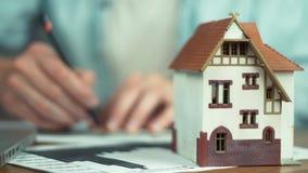 Modell av huset på tabellen Ung arkitekt som skapar byggprojekt stock video
