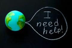 modell av jordplaneten på en svart tavla med behovshjälpen för inskrift I, miljö- begrepp royaltyfri illustrationer