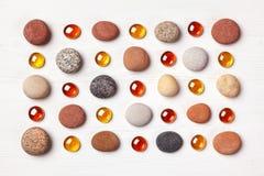 Modell av kulöra kiselstenar och orange glass pärlor på vit träbakgrund Lekmanna- lägenhet, bästa sikt fotografering för bildbyråer