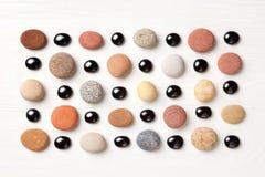 Modell av kulöra kiselstenar och svarta glass pärlor på vit träbakgrund Lekmanna- lägenhet, bästa sikt Arkivbild