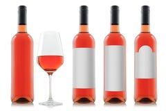 Modell av rosa vinflaskor med tomma vitetiketter och ett exponeringsglas av vin Arkivfoton