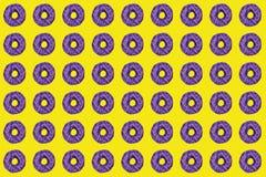 Modell av söta donuts med purpurfärgad fönsterrutor på gul bakgrund royaltyfri foto