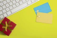 Modell av två tomma färgkreditkortar, gåvaask på det tomma gula skrivbordet r Royaltyfria Bilder