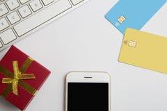 Modell av två tomma färgkreditkortar, smartphone, gåvaask på det tomma vita skrivbordet Affärsmodellbakgrund för Royaltyfria Bilder