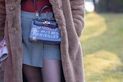 Modell, das einen überprüften Minischwarzweiss-rock und eine Handtasche trägt stockfotos
