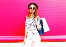 Modell der eleganten Frau mit den Einkaufstaschen, die einen schwarzen Hut tragen stockfotos