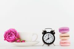 Modell der Kaffeetasse mit rosafarbener Blume, Makrone und Wecker auf weißem Schreibtisch mit sauberem Raum für Text und entwerfe Lizenzfreie Stockfotografie