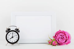 Modell der verzierten rosafarbenen Blume des Bilderrahmens und Wecker auf weißer Tabelle mit leerem Raum für Text und entwerfen I Stockfotografie