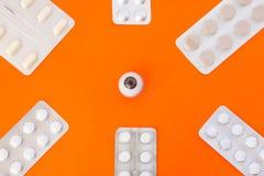 Modell des Auges umgeben durch sechs Blisterpackungen mit weißen Pillen nach innen in den Ecken des Bildes auf orange Hintergrund Stockbilder