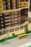 Modell des Baus eines Wohngebäudes mit Blick auf die Straße und einen gelben Bus Lizenzfreie Stockfotografie