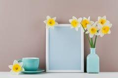 Modell des Bilderrahmens verzierte Narzissenblumen im Vase und in der Kaffeetasse mit sauberem Raum für Text Ihr blogging Stockfoto