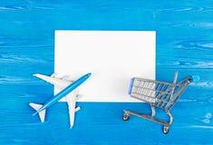 Modell des Flugzeuges, Lebensmittelgeschäftwarenkorb und leeres Blatt Papier auf dem blauen hölzernen Hintergrund kleines Auto au Lizenzfreie Stockfotos