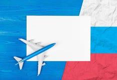 Modell des Flugzeuges, des leeren Blattes Papier und der Flagge von Russland auf dem blauen hölzernen Hintergrund kleines Auto au Lizenzfreie Stockbilder