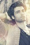 Modell des gutaussehenden Mannes entspannte sich das Stillstehen auf einem Baumstamm lizenzfreies stockfoto