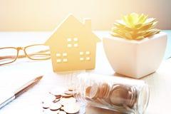 Modell des hölzernen Hauses, Sparkontobuch oder Finanzberichte und Münzen zerstreuten vom Glasgefäß auf Schreibtischtabelle stockfotos